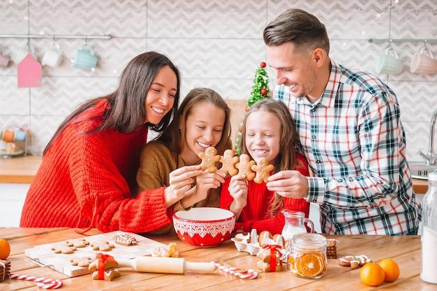 Rodzina z dziećmi z piernikiem na boże narodzenie w kuchni. wesołych świąt i wesołych świąt.