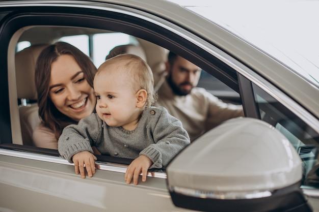 Rodzina z dziewczyną bbay wybierającą samochód w salonie samochodowym