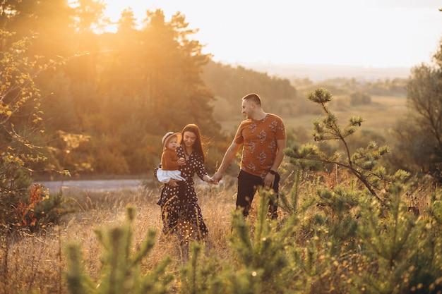 Rodzina z ich małą córeczką w polu jesienią