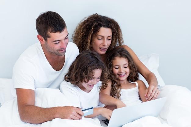 Rodzina z kartą kredytową robi zakupy online na łóżku