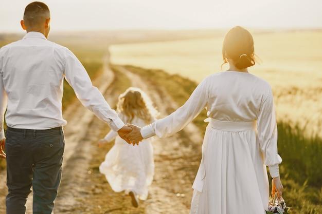 Rodzina z małą córeczką spędzać razem czas w słonecznym polu