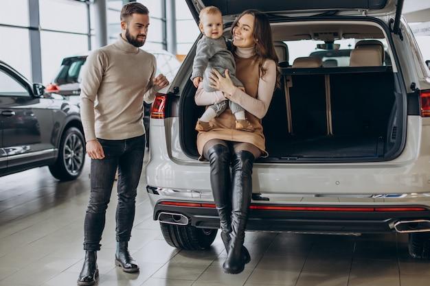 Rodzina z małą dziewczynką wybierającą samochód w salonie samochodowym