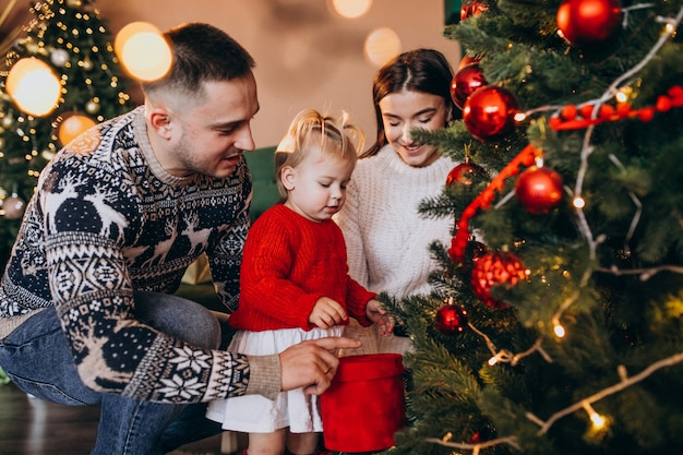 Rodzina z małym córki obwieszeniem bawi się na choince