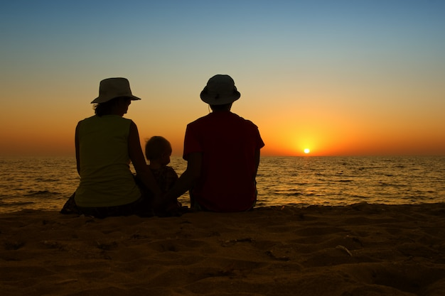 Rodzina z małym dzieckiem siedzi wpólnie na zmierzch plaży. koncepcja podróży rodzinnych.
