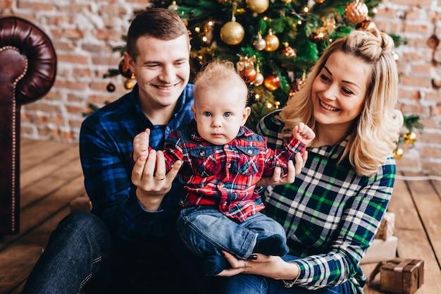 Rodzina z małym dzieckiem w pobliżu choinki