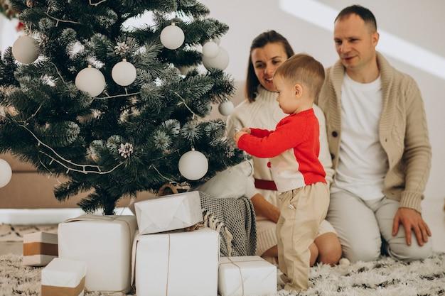 Rodzina z małym synkiem na boże narodzenie przy choince w domu
