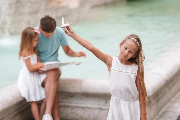 Rodzina z mapą turystyczną w pobliżu fontana di trevi, rzym, włochy.