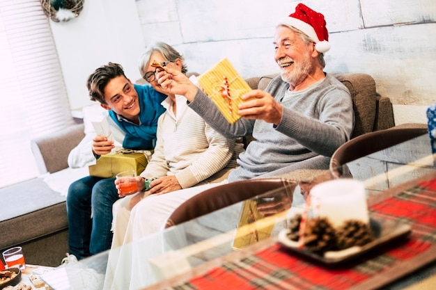 Rodzina z nastolatkiem i dziadkami siedziała przy kanapie w domu w świąteczny poranek śmiejąc się i otwierając swoje prezenty z wielką miłością i czułością