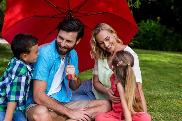 Rodzina z parasolowym obsiadaniem na trawie przy jardem