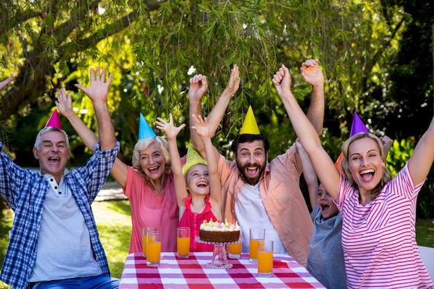 Rodzina z podniesionymi rękami ciesząc urodziny na podwórku