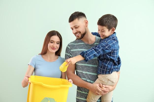 Rodzina z pojemnikiem na śmieci. pojęcie recyklingu