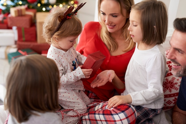 Rodzina z prezentem bożonarodzeniowym w łóżku