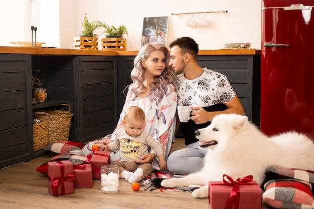 Rodzina z psem samoyedem ciesząca się wspólnym czasem spędzonym w domu w kuchni w okresie świątecznym