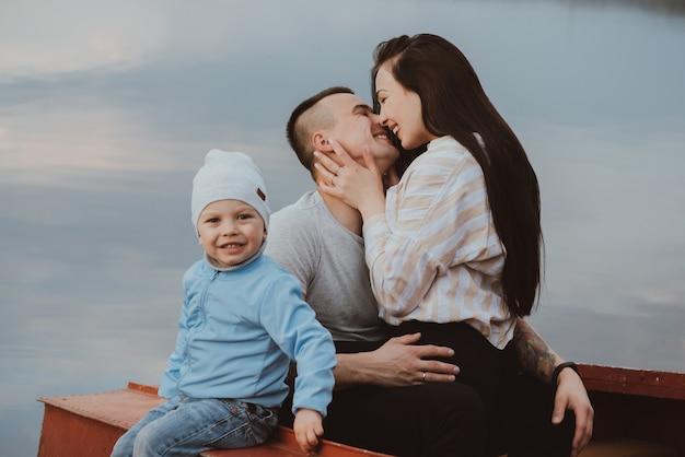 Rodzina z synem siedzą latem w łodzi nad wodą