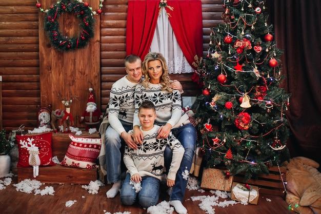 Rodzina z synem w stroju pandy w pobliżu choinki uroczy uścisk