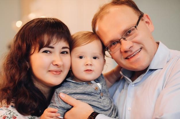 Rodzina z synkiem przytula się w zbliżeniu.
