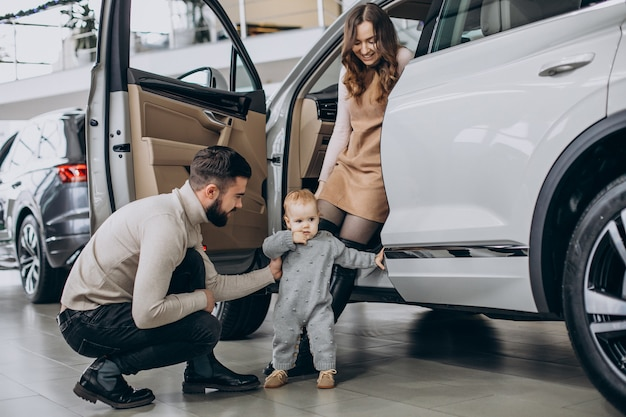 Rodzina z uroczą córką wybiera samochód w salonie samochodowym