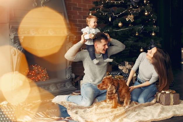 Rodzina z uroczym psem w domu w pobliżu choinki