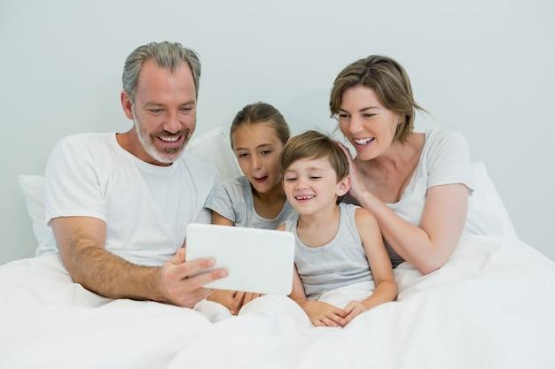Rodzina za pomocą cyfrowego tabletu na łóżku w sypialni w domu