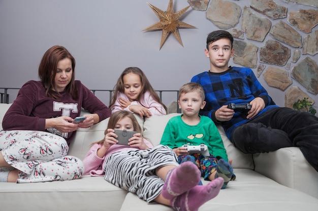 Rodzina za pomocą technologii na kanapie