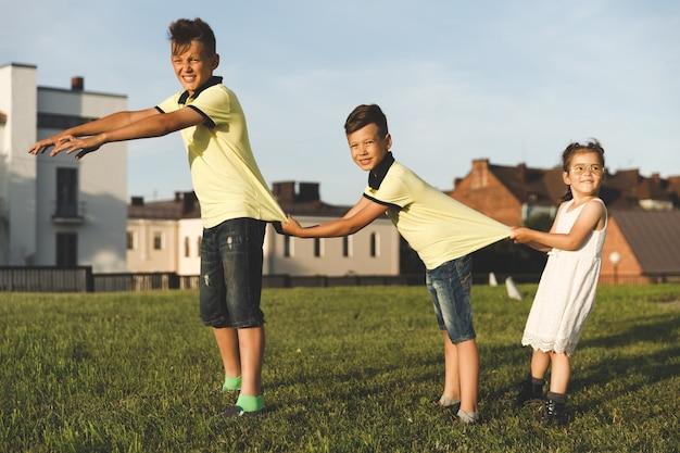 Rodzina zabawy na łonie natury. dwóch braci z siostrą