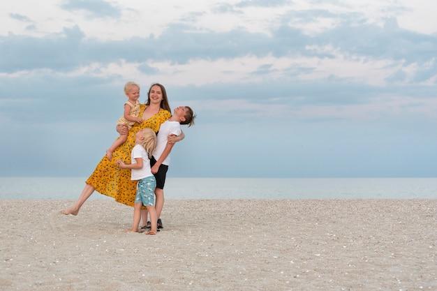 Rodzina zabawy na wakacjach. mama i troje dzieci nad morzem.