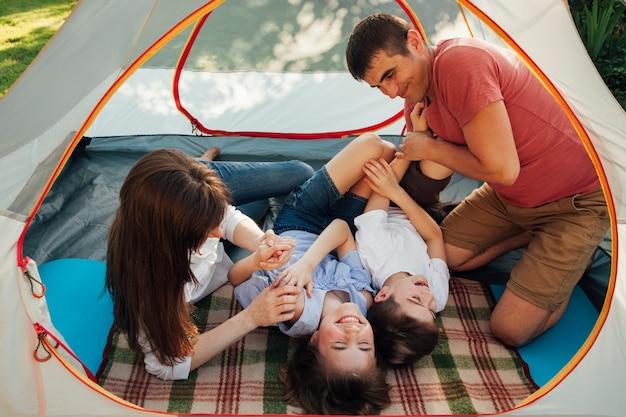 Rodzina zabawy w namiocie na wakacjach kempingowych
