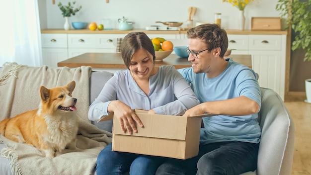 Rodzina zadowolona z szybkiej dostawy. rozpakowanie zamówienia ze sklepów internetowych. szczęśliwa rodzina otwiera odebraną paczkę w dużym kartonie. rodzinne zakupy razem.