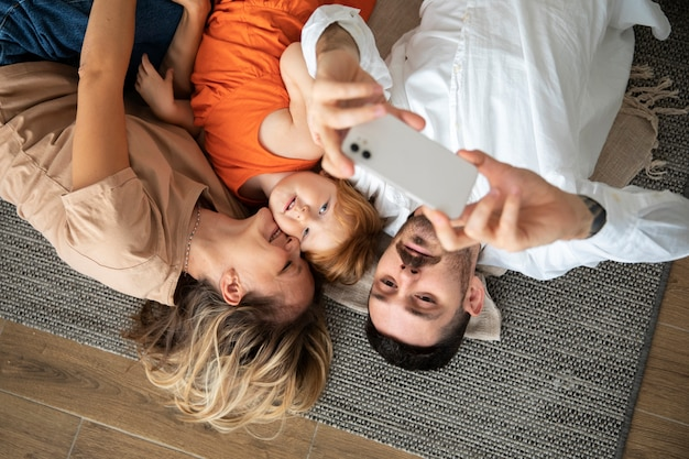 Rodzina ze średnimi zdjęciami robi selfie za pomocą smartfona