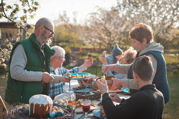 Rodzina zebrała się przy świątecznym stole w ogrodzie, aby uczcić wielkanoc