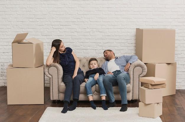 Rodzina zmęczona po spakowaniu kartonów
