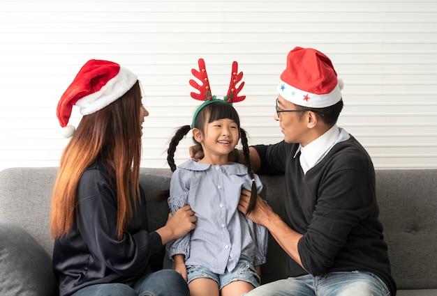 Rodzinna azjata matka, ojciec z córek szczęśliwymi bożymi narodzeniami wpólnie w pokoju dziennym w domu i.