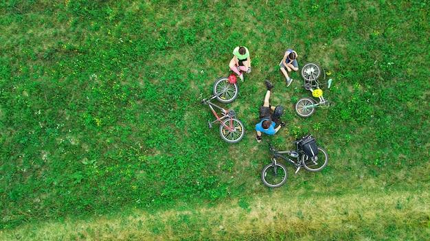 Rodzinna jazda na rowerze na rowerach widok z lotu ptaka, szczęśliwi aktywni rodzice z dzieckiem bawią się i odpoczywają na trawie, rodzinny sport i fitness w weekendy