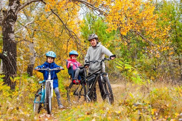 Rodzinna jazda na rowerze w złotym jesiennym parku, aktywny ojciec i dzieci jeżdżą na rowerach, rodzinny sport i fitness z dziećmi na świeżym powietrzu