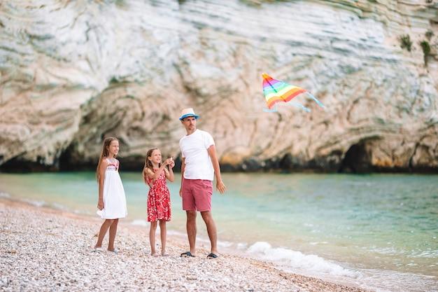 Rodzinna latająca latawiec razem na tropikalnej plaży biały