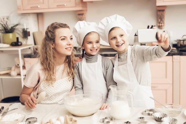 Rodzinna mama dzieci biorą selfie gotowanie w kuchni.
