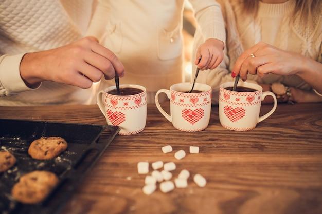 Rodzinna mama, tata i córka w białych swetrach gotują i piją kakao z piankami
