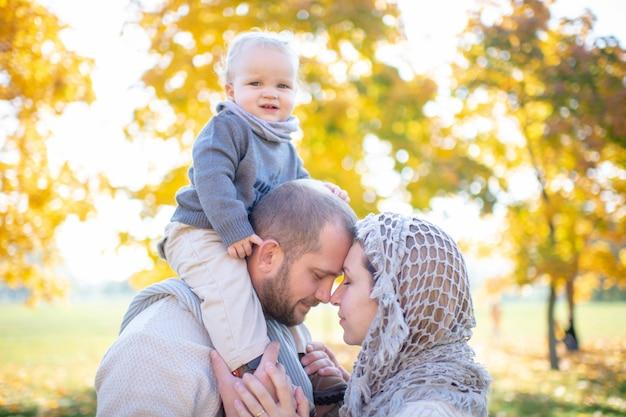 Rodzinna para ściska na zewnątrz z opiekunką na ramionach ojców