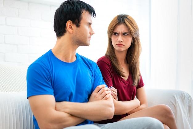 Rodzinna para siedzi na kanapie, nie rozmawiając po kłótni, młody mąż jest zmęczony ciągłymi kłótniami urażonej kobiety, która odwróciła się plecami do chłopaka z rękami w poprzek.