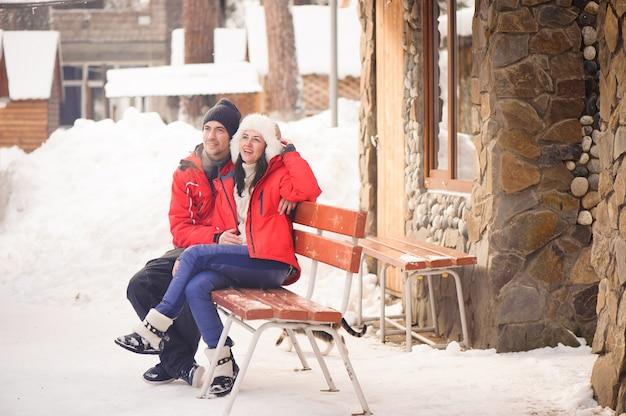 Rodzinna para w zimy odzieżowym obsiadaniu na drewnianej ławce