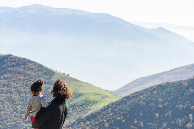 Rodzinna podróż razem na szczycie wysokiej góry na zewnątrz, patrząc na piękny krajobraz