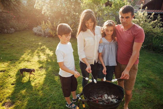 Rodzinna pozycja blisko grilla i prażaka marshmallow w parku