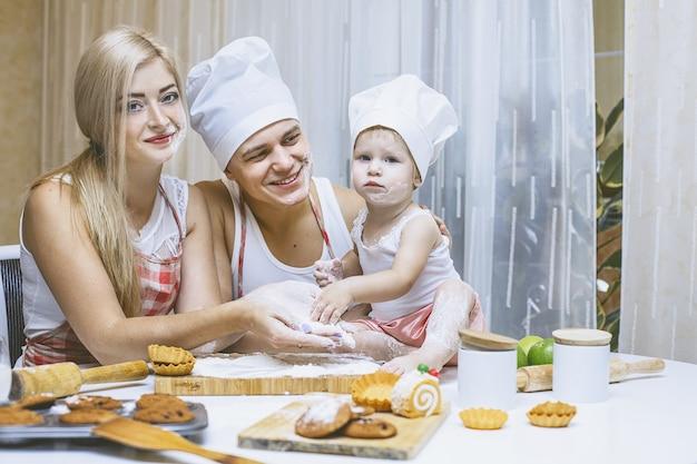 Rodzinna szczęśliwa córka z tatą i mamą w domowej kuchni, śmiejąc się i przygotowując razem jedzenie