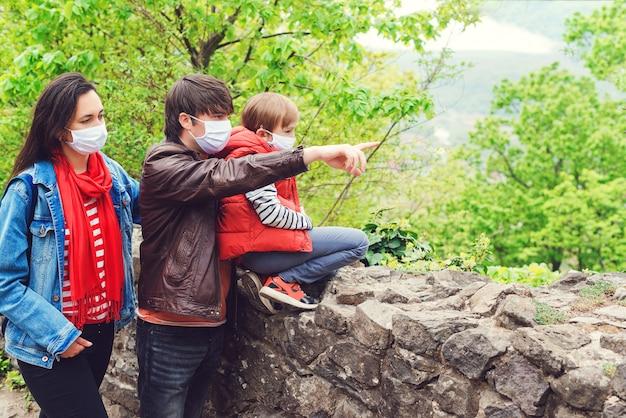 Rodzinna wycieczka do starego zamku. koronawirus kwarantanna. rodzice z synem na sobie maski na zewnątrz.