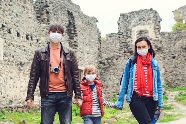 Rodzinna wycieczka do starego zamku. rodzice z synem na sobie maski na zewnątrz.
