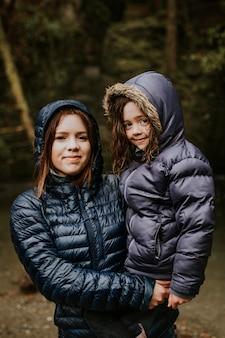 Rodzinna wycieczka na kemping matka trzymająca córkę w ramionach
