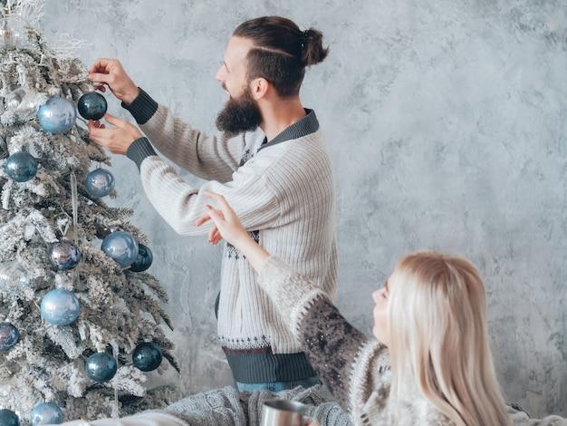 Rodzinne ferie zimowe. szczęśliwa para dekorowanie jodły niebieskimi szklanymi kulkami.