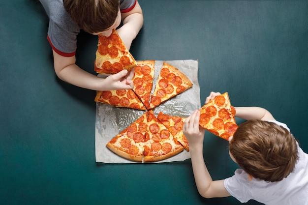 Rodzinne jedzenie pizzy peperoni. dzieciaki trzyma kawałek pizzy.