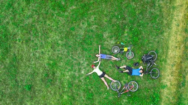 Rodzinne kolarstwo na rowerach na zewnątrz widok z lotu ptaka, szczęśliwi aktywni rodzice z dzieckiem bawią się i relaksują na trawie, rodzinnym sporcie i fitnessie w weekend
