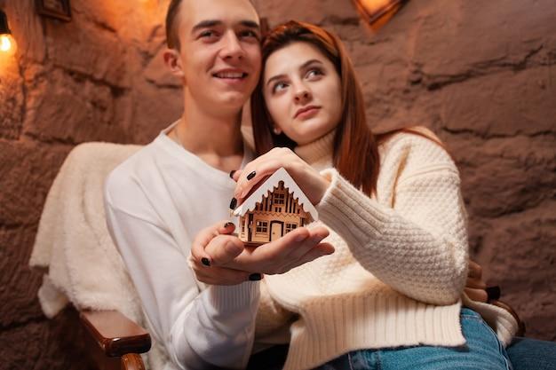 Rodzinne marzenia o własnym domu. boże narodzenie. młodzi ludzie trzymają dom.